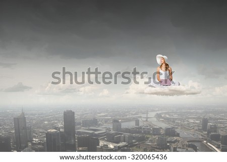 Young lady sitting on cloud with laptop on knees - stock photo
