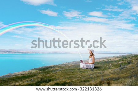 Young lady sitting on green grass with laptop on knees - stock photo