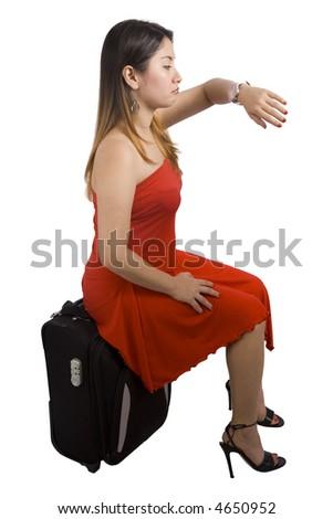Young lady sitting on her suitcase and looking at her watch
