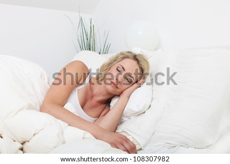 Young lady sleeping peacefully in bed Natural pose of an attractive young lady sleeping peacefully in bed surrounded by white bedclothes - stock photo