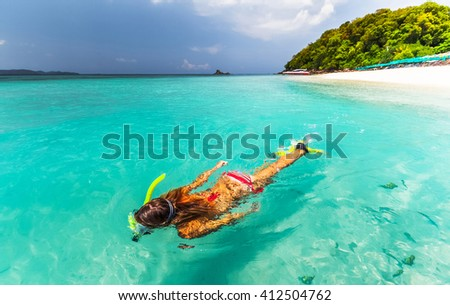 Young lady snorkeling in a tropical sea near sandy beach - stock photo