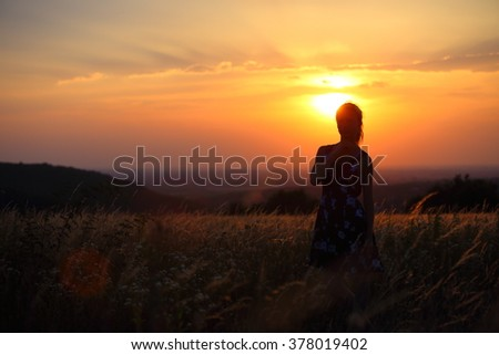 Young lady standing alone in a field during sunset. Silhouette of a thinking woman.