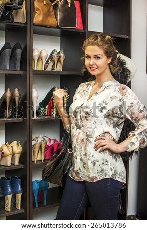 Young lady standing in front of shoes in her shoe closet or a shoe store. - stock photo