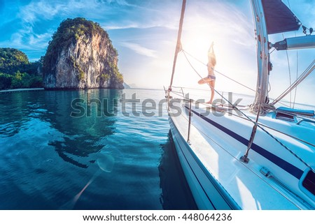 Young lady standing on the bow of yacht and doing stretching exercises at sunrise