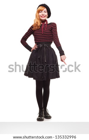 young lady standing on the edge of a platform showing something with her finger isolated on white background - stock photo