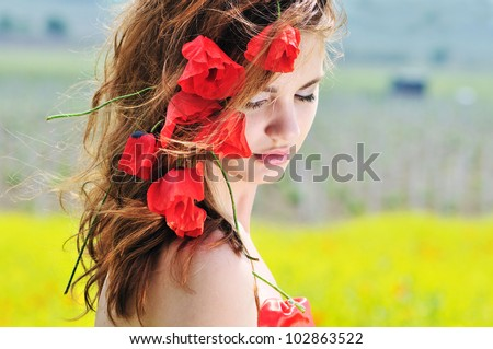 young lady standing with poppies in her hair - stock photo