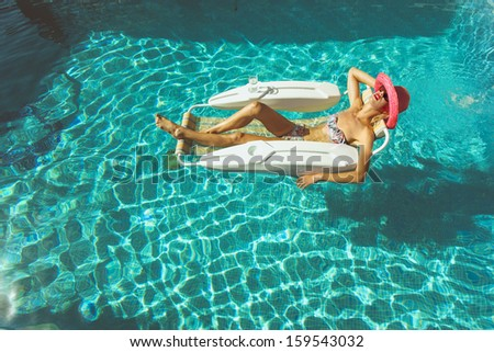 Young lady sunbathing in pool on a hot summers day - stock photo
