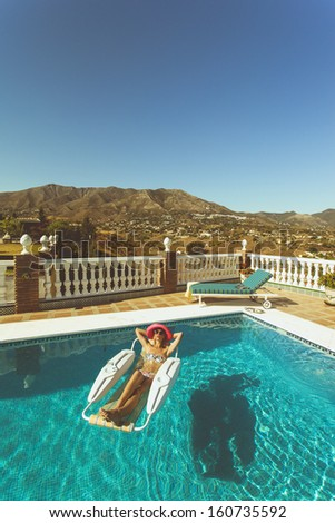 Young lady sunbathing in pool on a hot summers day in the spanish mountains - stock photo