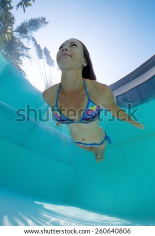 Young lady swimming underwater in the pool - stock photo