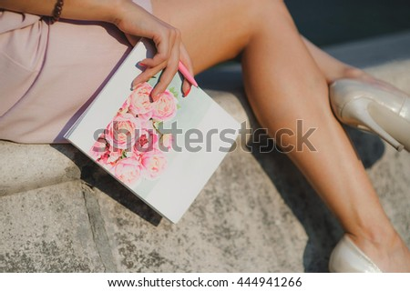 young lady with a notebook on her sun burnt legs. summer evening sunset