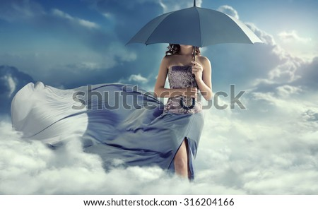 Young lady with an umbrella walking in the clouds - stock photo