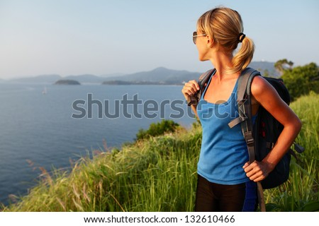 Young lady with backpack standing on a lush tropical meadow and looking to horizon - stock photo