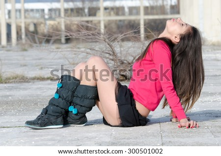 Young lady with boots and very short skirt sitting cross-legged