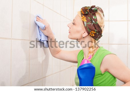 young lady with hairband cleaning the tiles with a cleaning towel - stock photo