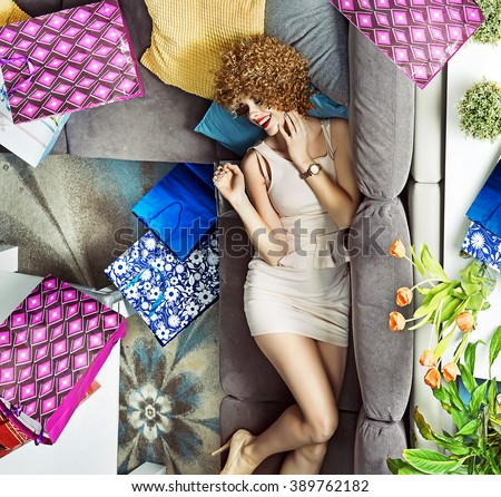 Young lady with many shopping bags lying on the sofa