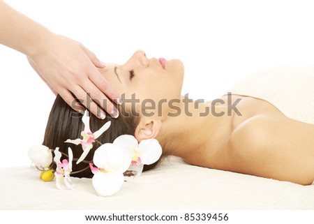 Young lady with orchid enjoying massage at spa salon