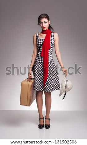 young lady with retro strap plaid dress carrying a suitcase on her hand and a hat on her other hand,waiting for her vehicle on grey background - stock photo