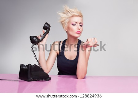 young lady with short blond hair holding handset and not listening the phone - stock photo
