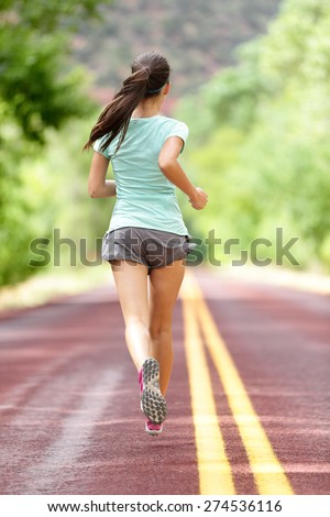 Young lady working out running away on rural road. Woman runner athlete training jogging during workout outside. Full body length rear view showing back. Girl in shorts and running shoes. - stock photo