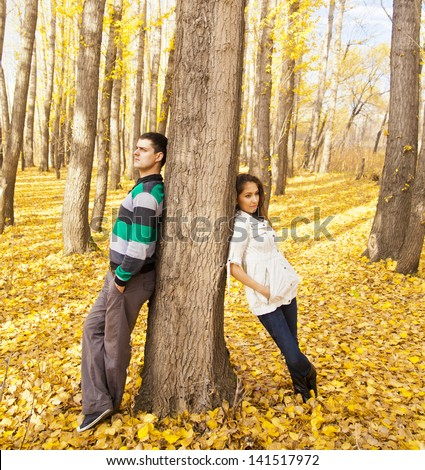 Young latin hispanic full length couple behind a tree an autumn   symbol of quarrels misunderstandings depression divorce and separation hurt parting  Space for inscription - stock photo