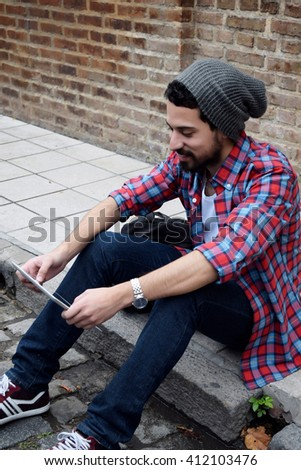 Young latin man using a tablet on the street. - stock photo
