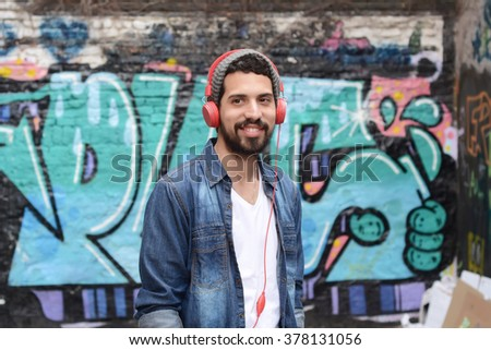 Young latin man with red headphones. Trendy and urban style, - stock photo