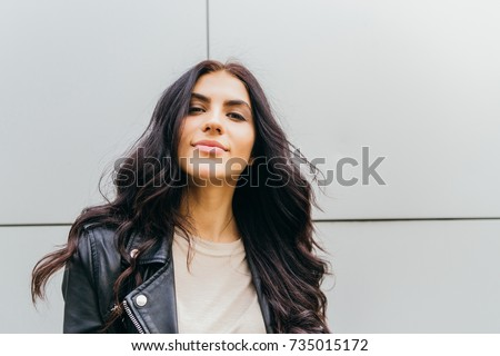 young latin woman walking with happy emotion on grey wall