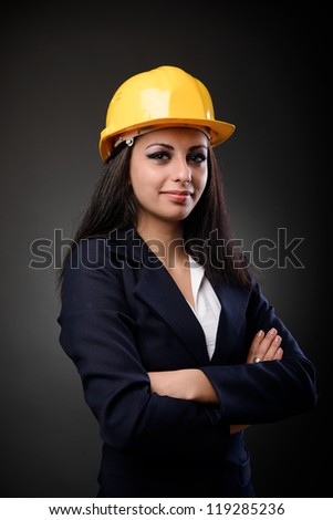 Young latino construction woman with hardhat and arms folded - stock photo