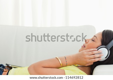 Young Latino listening music on a smartphone while lying on a sofa