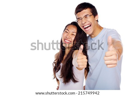 Young laughing couple showing thumb up hand gesture isolated on white background - stock photo