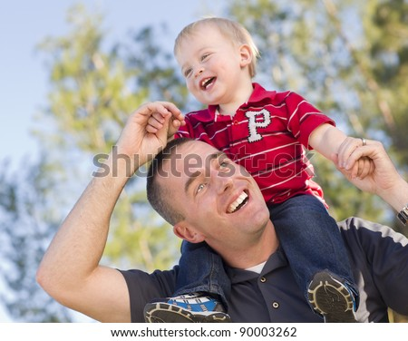 Young Laughing Father and Child  Having Piggy Back Fun.