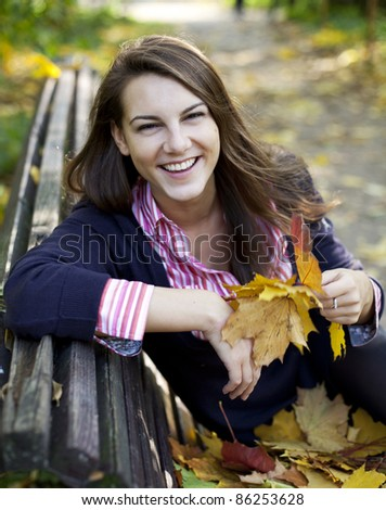 Young laughing girl sitting on bench in park holding fallen leaves - stock photo