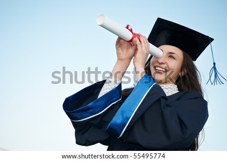 Young laughing graduate girl student in gown looking through diploma outdoors - stock photo