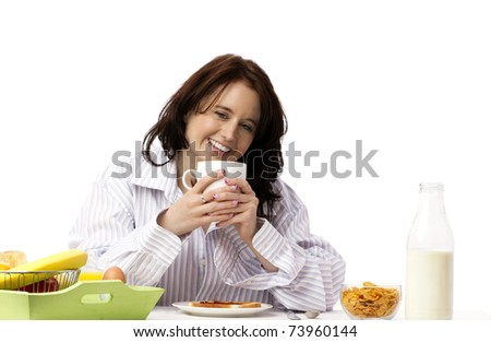 young laughing woman holding coffee mug at breakfast - stock photo