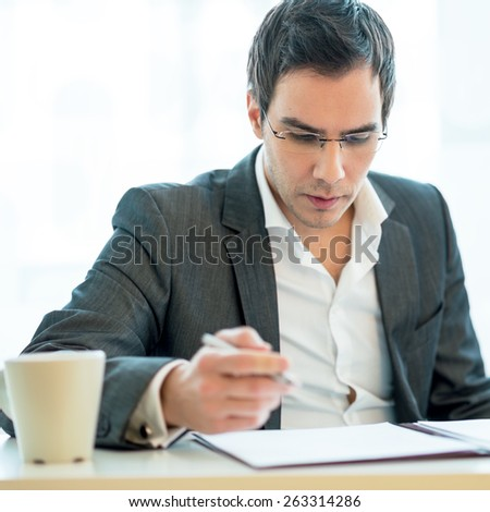 Young lawyer wearing glasses attentively reading legal documents at his desk. - stock photo