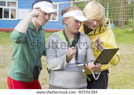 Young leaders of summer camp discuss something holding the notebook in hands