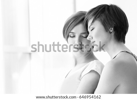 Young lesbian couple standing near window