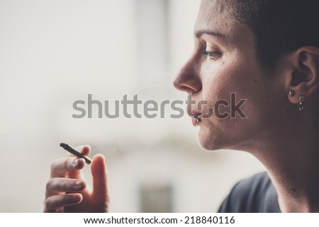 young lesbian stylish hair style woman smoking at home