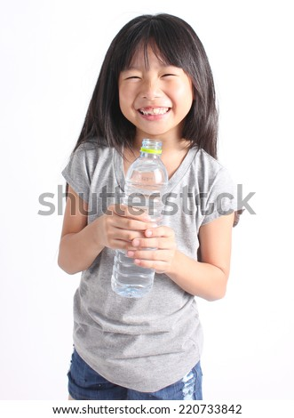 Young little girl holding a bottle of water.  - stock photo
