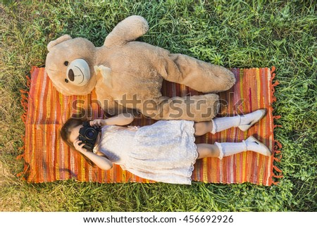 Young little girl photographer with old vintage film photo camera laying down on picnic blanket with teddy bear taking picture outdoor. Children's play. Art or creativity concept. - stock photo