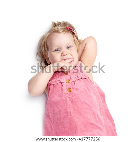 Young little girl with curly hair in pink dress lying over isolated white background - stock photo