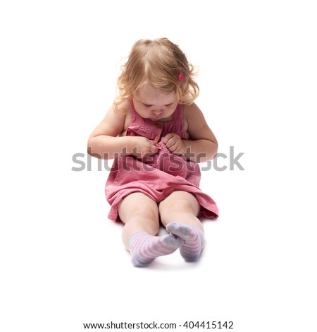 Young little girl with curly hair in pink dress sitting over isolated white background - stock photo