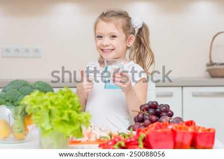 Young little pretty smiling girl shows a thumbs up and gives you the glass with clean fresh water - stock photo
