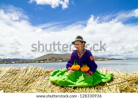 Young local girl on a floating Uros island standing in front of her home, lake Titicaca - stock photo