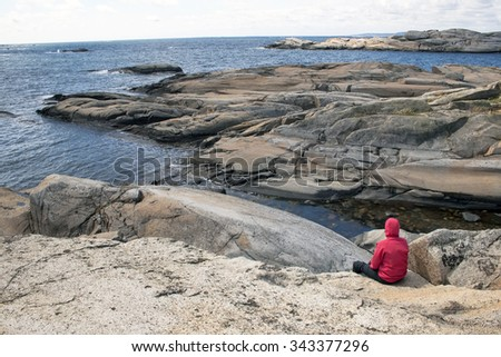 Young lonely man sitting over the sea at the rock Verdens Ende, World's End, or The End of the Earth is located at the southernmost tip of the island of Tjome in Vestfold, Norway. - stock photo