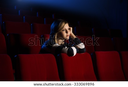 Young lonely woman at the cinema leaning on the seat in front of her and watching a movie - stock photo