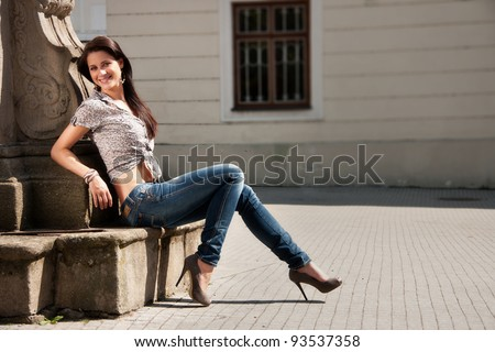 Young long hair attractive brunette in a sitting pose - stock photo