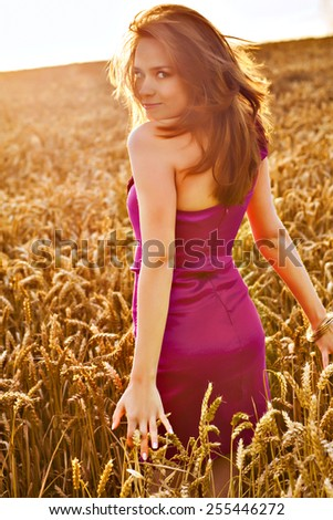 Young long hair girl in red dress walking in wheat field - stock photo