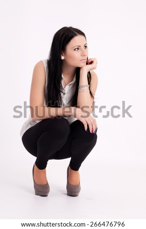 Young long-haired black-haired woman squatting thoughtful - stock photo