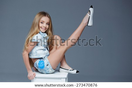 Young long haired girl in short and shirt sitting on a chair in studio - stock photo